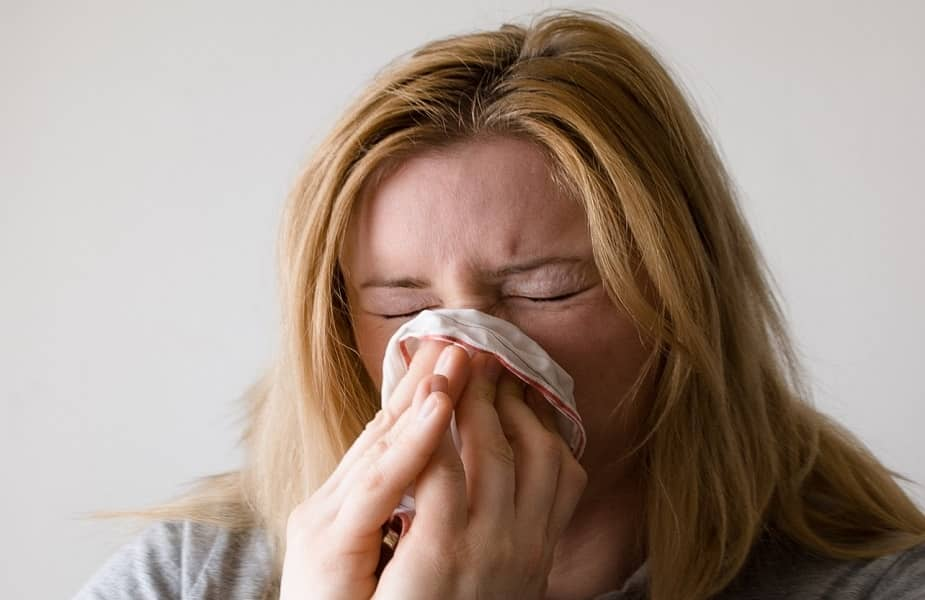 woman sneezing due to morning allergies