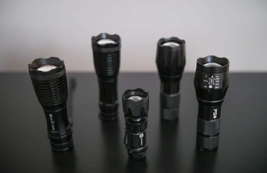 Six Tactical Flashlights On a Table