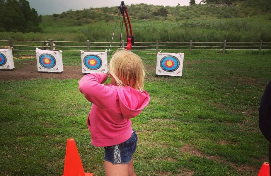 Small Woman Shooting a Bow at a Target