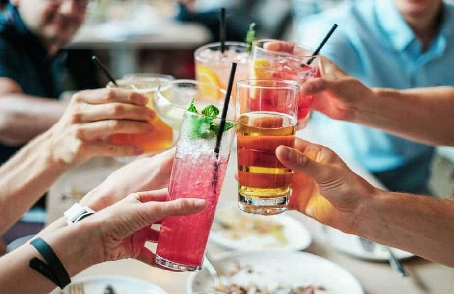 Four People Touching their Drinks Together at a Table