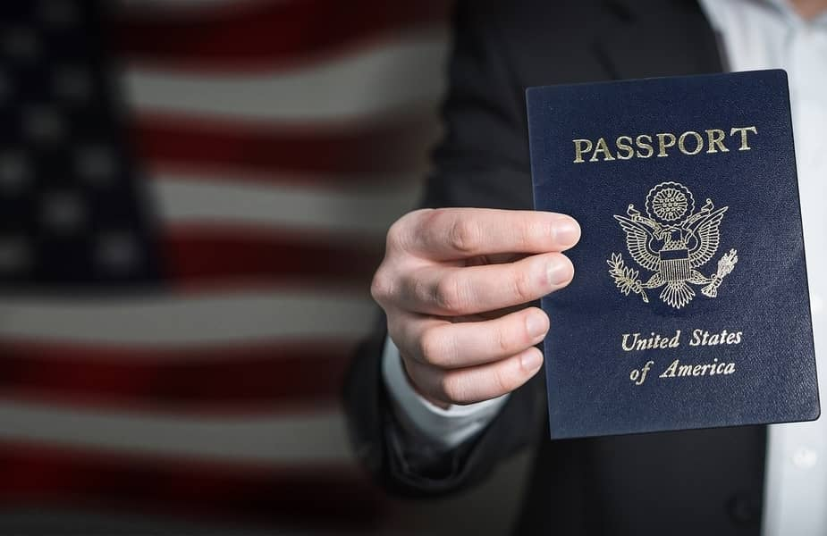 Hand Holding a Passport with American Flag in the Background