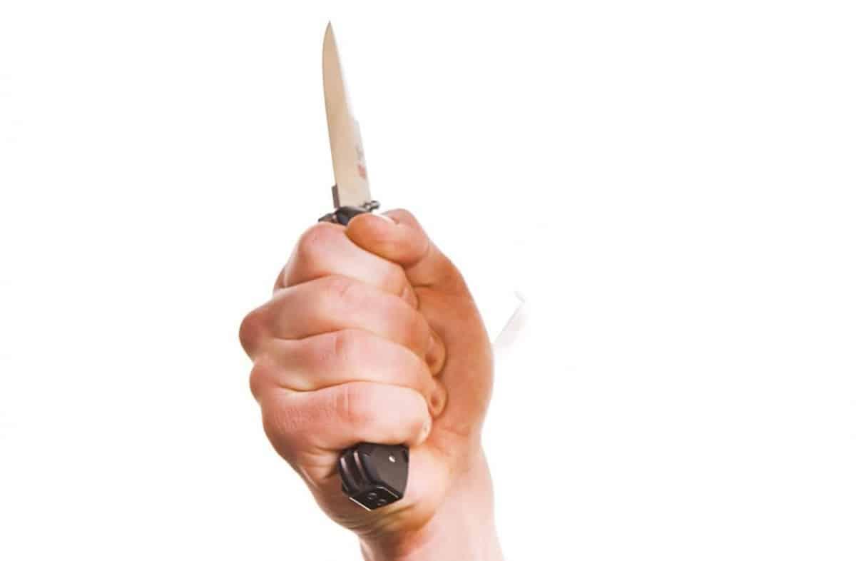 Hand Holding a Pocket Knife Threateningly