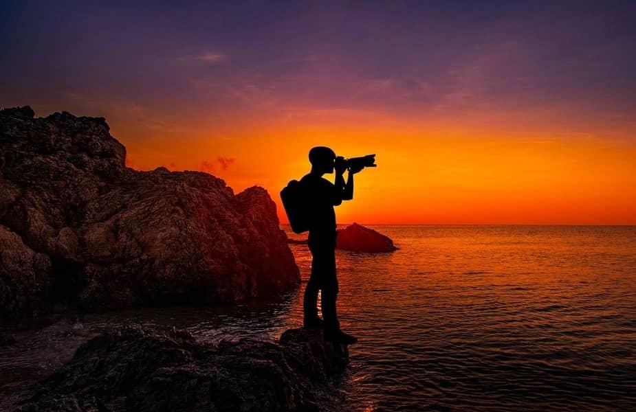 Photographer Taking Sunset Photographs of Ocean