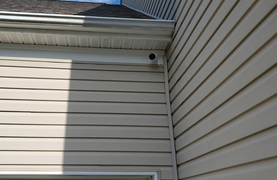 Security Camera Installed on Vinyl Siding Above a Garage Door