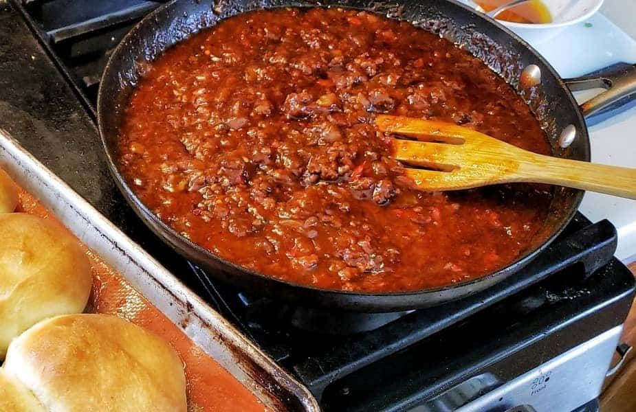 Sloppy Joes Being Made on a Stove With Homemade Buns Next to It