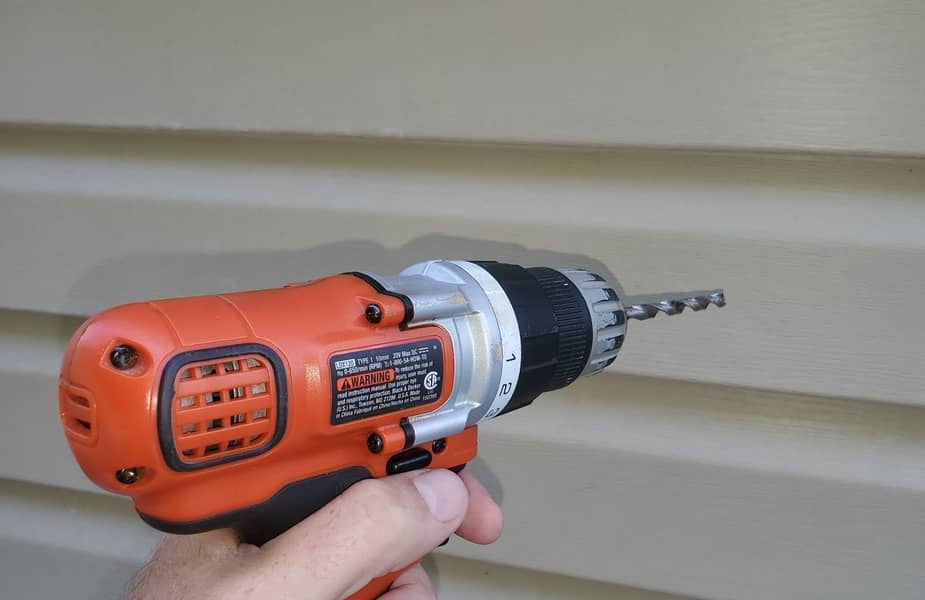 Electric Drill About to Drill Into Vinyl Siding