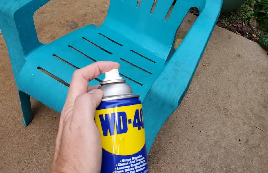 Spraying WD40 on a Blue Plastic Chair