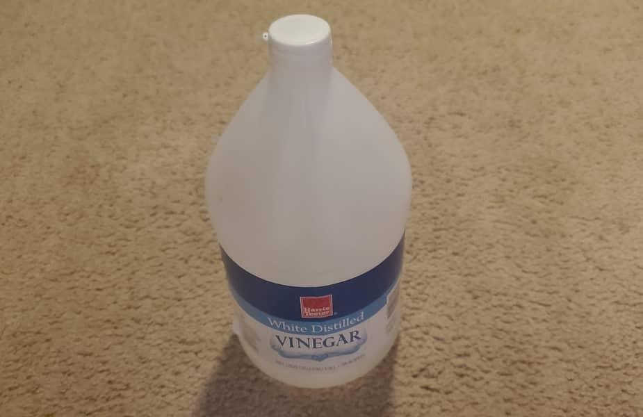 A Bottle of White Distilled Vinegar on Carpet