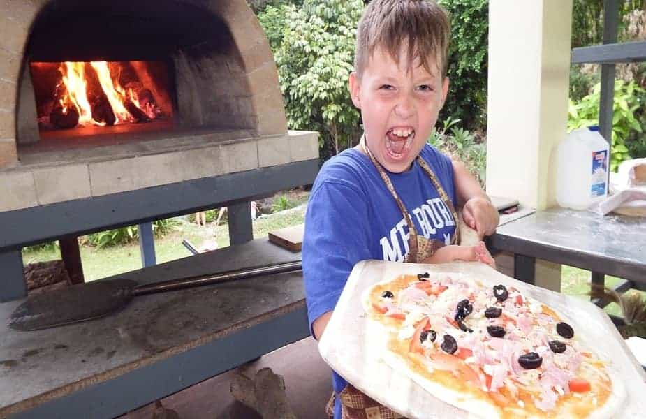 Kid Holding a Pizza in Front of an Oven
