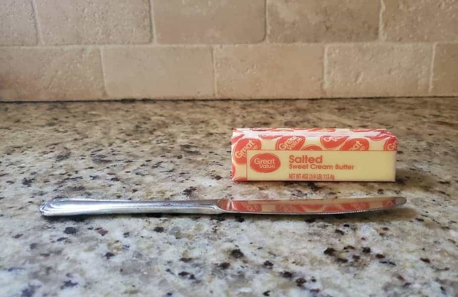 A Stick of Butter on the Counter With a Butterknife in Front