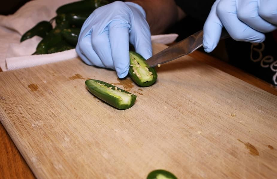 Fresh Jalapeno Pepper Being Cut on a Cutting Board