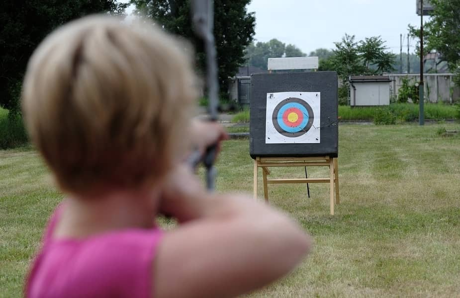 Over the Shoulder of a Woman Shooting a Bow and Arrow at a Target
