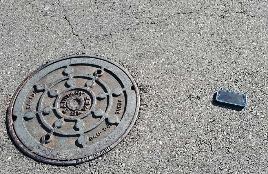 Phone on Street Next to a Manhole Cover