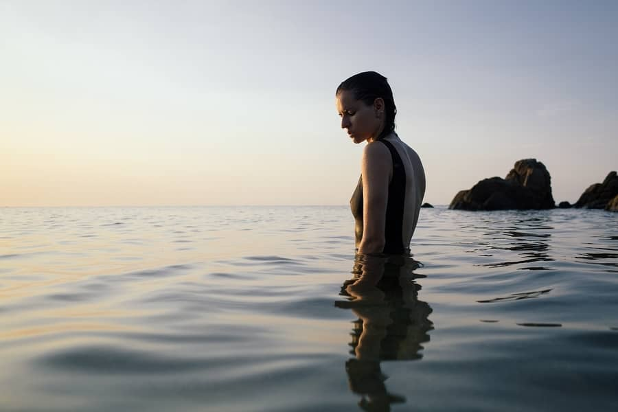 Woman Wading Out Into the Ocean