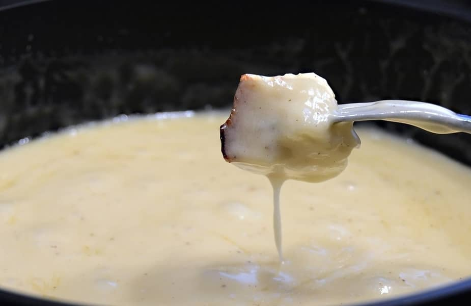Bread Being Dipped Into White Cheese Dip Fondue