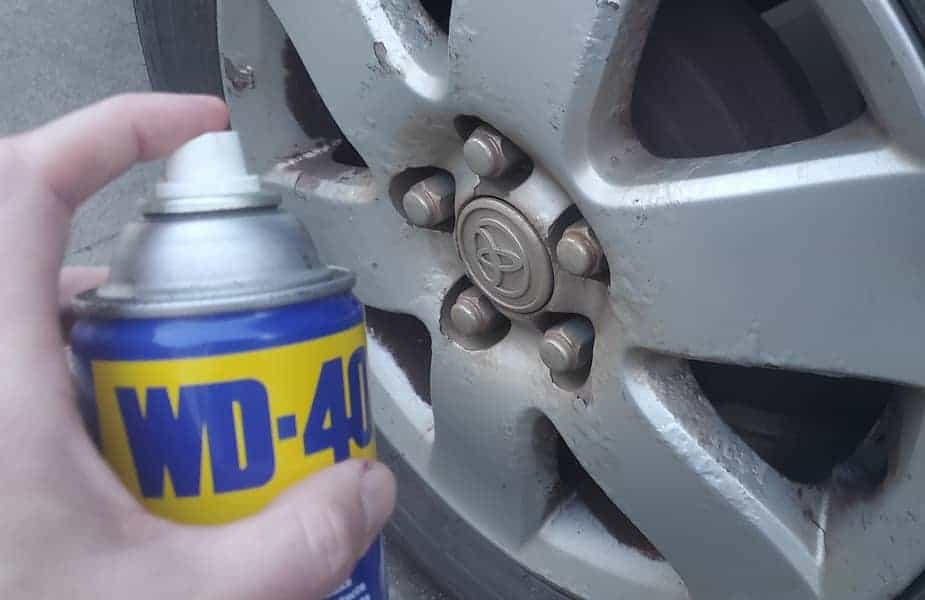 Spraying WD-40 on a Corroded Wheel and Lugnuts