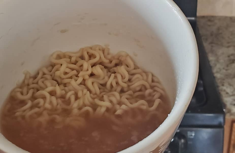Cup of Ramen in Front of a Stove
