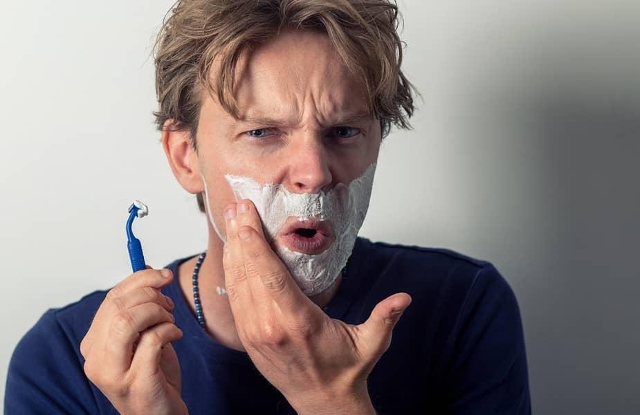 Man Shaving and Complaining of Razor Burn