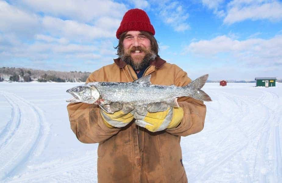 Man Holding a Frozen Fish Caught Ice Fishing