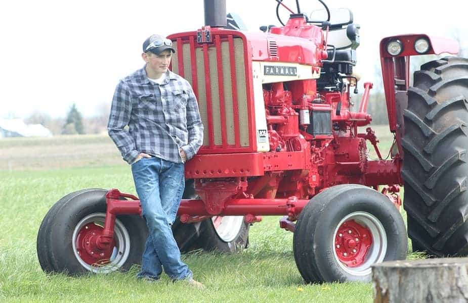Youth-Standing-in-Front-of-a-Farming-Tractor