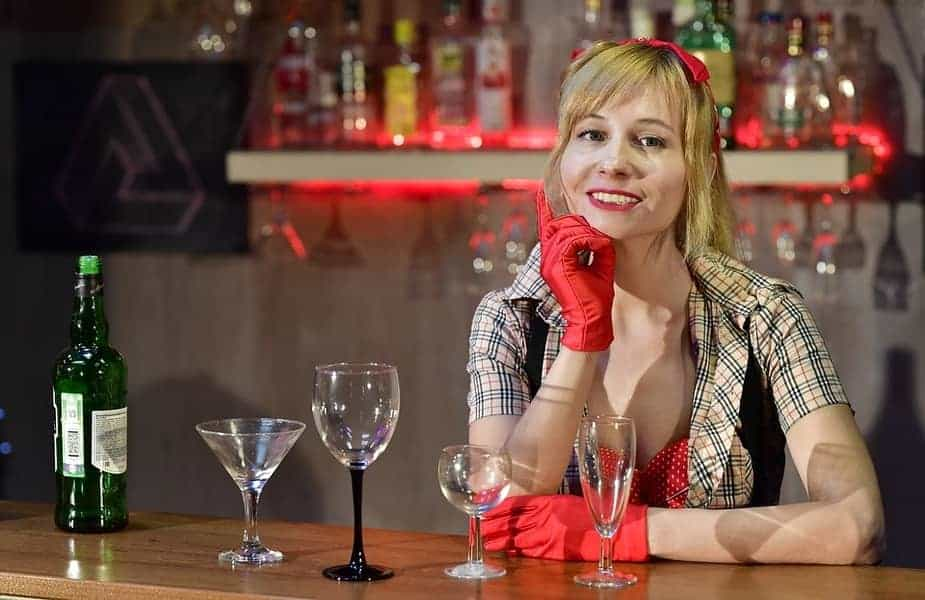Woman Bartender With Empty Glasses in Front of Her